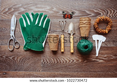 Spring gardener table top view with tools, gloves, peat pots and garden labels on brown wooden background. Flat lay composition, seasonal preparations for sawing seeds #1022730472