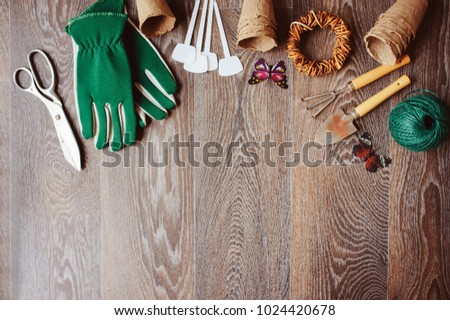 Spring gardener table top view with tools, gloves, peat pots and garden labels on brown wooden background. Flat lay composition, seasonal preparations for sawing seeds #1024420678