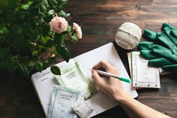 spring gardening planning, envelopes with seeds, gardening gloves against wooden table
