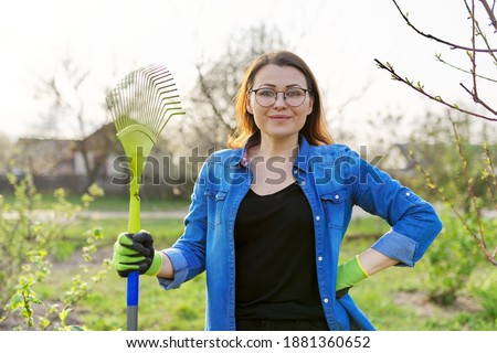 Spring gardening, portrait of mature smiling woman gardener with rake looking at camera. Trees and bushes background, seasonal cleansing of last year's grass and leaves in the garden, backyard Photo stock ©