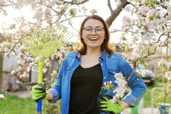 Spring gardening, portrait of mature smiling woman with rake looking at camera. Blooming trees in the garden background, seasonal cleaning in the garden, hobbies and leisure