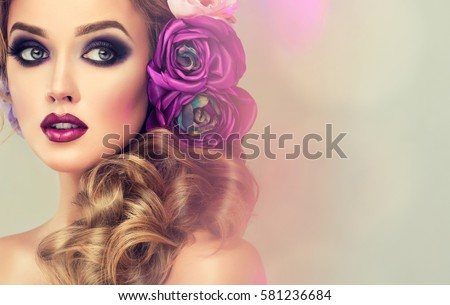 Spring  girl with trendy make up  smoky eyes .  Hairstyle curly ponytail with violet   artificial rose flowers on the head. #581236684