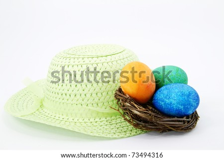 Spring green Easter bonnet with light green ribbon sits with Easter eggs dyed  orange, green, and blue