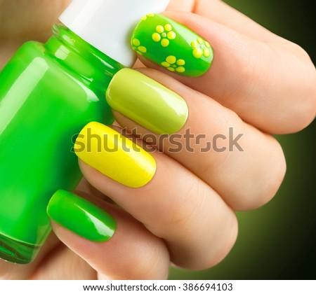 Spring green manicure. Fresh Nature trendy green nails. Beautiful nail polish with grass. Green and yellow colors Eco Nail art manicure. Bottle of Nail Polish. Fashion Beauty hands. Stylish Nailpolish