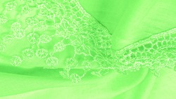 Spring green silk with lace capes. Smooth elegant green silk or luxe satin can be used as an abstract background. Background texture, postcard template