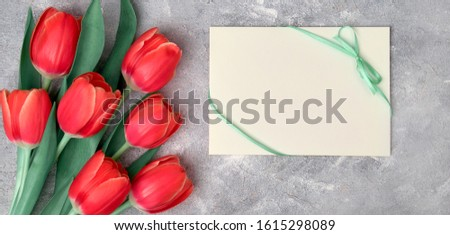 Spring greetings, flat lay with red tulips and blank paper card on grey textured background. Easter, Mother's day, Birthday or Anniversary, gender neutral panoramic greeting design.