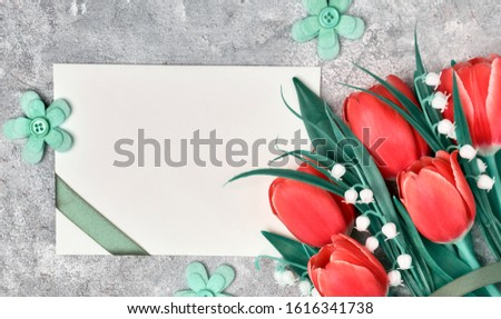 Spring greetings, flat lay with red tulips and blank paper card on grey textured background. Easter, Mother's day, Birthday or Anniversary, gender neutral greeting design.