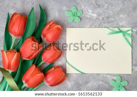 Spring greetings, flat lay with red tulips, green textile flowers and blank paper card on grey textured background. Easter, Mother's day, Birthday or Anniversary, gender neutral greeting design.