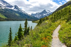 Spring Hiking Trail - A spring view of a hiking trail at shore of Lake Josephine, with Mount Gould and Allen Mountain rising at front and left, in Many Glacier of Glacier National Park, Montana, USA.