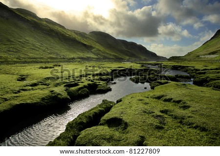 Spring in Scotland Valley: Infectious greens, winding streams, and volatile skies -- all typical of spring in Scotland.  Taken on Isle of Skye, in the Scottish Highlands.