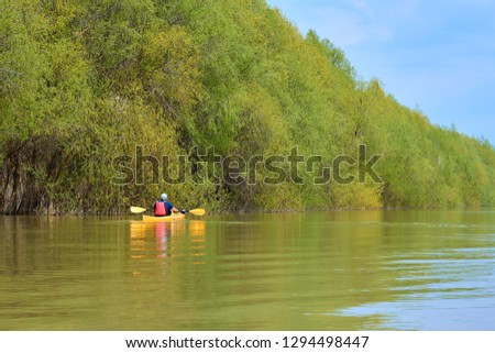 Spring kayaking. Concept for adventure, travel, action, lifestyle. Rear view of kayaker man paddle yellow kayak on Danube river.