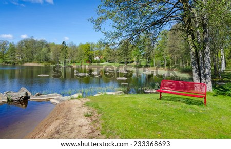 Spring lake panorama landscape with symbolic red bench