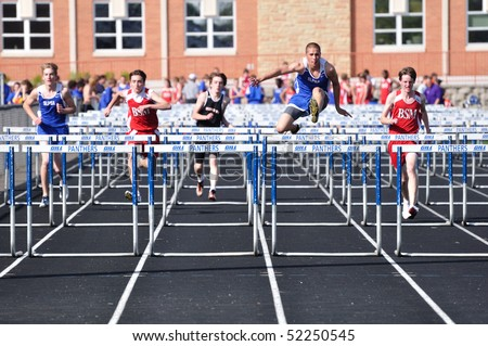SPRING LAKE PARK, MN - APRIL 20: Runners from Spring Lake Park, St. Louis Park, and Benilde-St. Margaret's complete in a high school boys hurdles race on April 20, 2010 in Spring Lake Park, Minnesota. - stock photo
