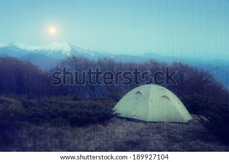 Spring landscape at night. Camping in the mountains in the moonlight. Tent in the mountains. Carpathians, Ukraine, Europe. Filtered image: vintage, grunge and texture effects