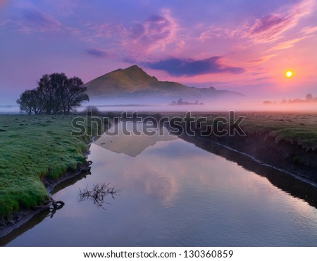 Spring landscape on the river near the mountains. Sunrise