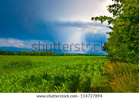 Spring landscape with a sunny weather on the right and rain on the left - stock photo