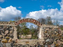 spring landscape with an old stone building wall and arched windows, the ruins of a building in a bright green field