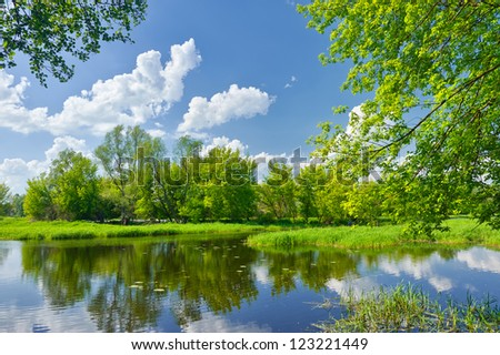 Spring landscape with Narew river and clouds on the blue sky