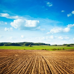 Spring Landscape with Plowed Field on the Background of Beautiful Clouds and Blue Sky. Ploughed Soil. Agriculture Concept. Copy Space.