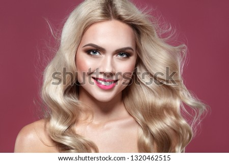 Spring make up. Purity Blonde haired Woman Portrait with blue eyes and Healthy Long Shiny Wavy hairtyle. Volume shampoo. Blond Curly permed Hair and bright makeup.  Beauty salon and haircare concept. #1320462515