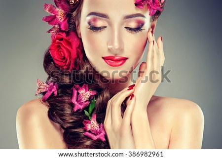 Spring model with flowers in her hair and fashion makeup . Summer girl with trendy make up and hairstyle .