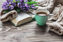 Spring morning coffee. A cup of coffee on a wooden table, an open book and a warm sweater against the background of a bouquet of spring flowers. Still life concept. Cozy morning.