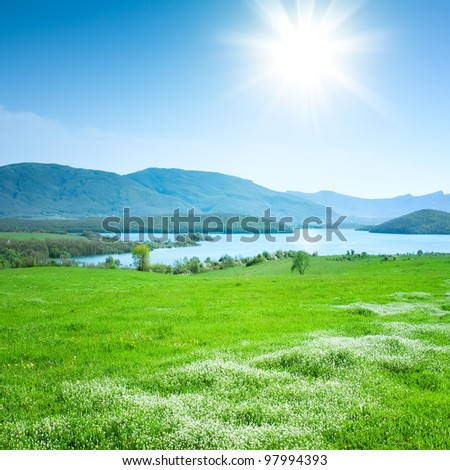 Spring mountain landscape with a lake and meadow