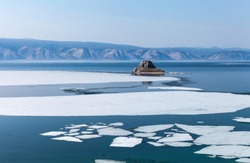 Spring on Baikal Lake. White ice floats floating on the blue water of the Small Sea Strait. Cormorants flew to the stone Edor islet
