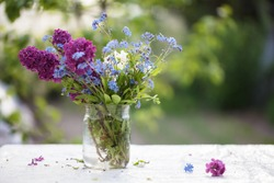 Spring or summer background. A bouquet of lilacs and forget-me-nots in a glass jar on the table. Beautiful flowers on a green background.