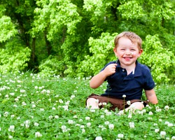 Spring or summer portrait of cute young boy playing with flower outdoors in clover field.