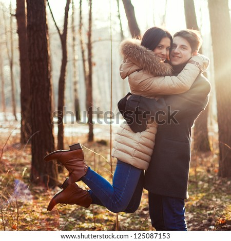Spring outdoor portrait of young pair. Boy and girl in the spring forest sitting on vintage cover