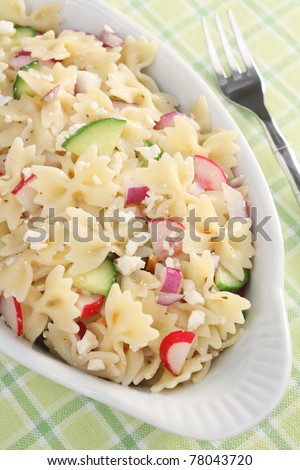 Spring Pasta Salad - Colorful pasta salad with bow-tie pasta, cucumbers, radishes, red onions, and feta cheese.