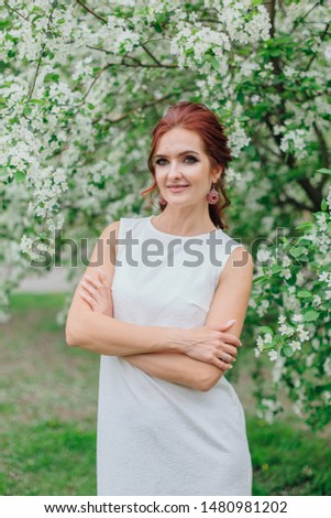 Spring portrait of a charming woman wearing beautiful white dress under the blooming apple tree.