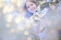 spring portrait of an adult happy woman in a blooming garden, sun rays and glare, april flowers girl