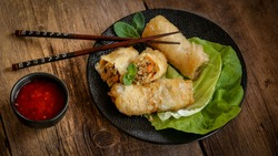 spring rolls and sweet chili sauce on a modern black plate on a wooden table