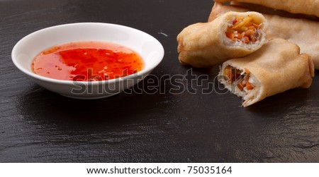 Spring rolls with sweet chili dipping sauce on dark grey slate background.