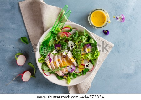 Spring salad with radishes, chicken breast and edible flower, selective focus #414373834