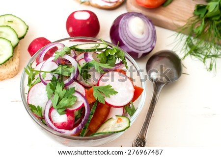 Spring Salad with radishes, cucumber, Chinese cabbage and red onion closeup in glass bowl on a white wooden background