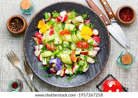 Spring salad with various vegetables and edible flowers. Diet food.Spring vitamin salad