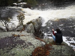 Spring scene featuring beautiful waterfalls, rocks with green lichens and bystander taking picture with cell phone