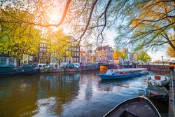 Spring scene in Amsterdam city. Tours by boat on the famous Dutch canals. Colorful evening landscape in Netherlands, Europe.