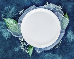 Spring season composition with a white plate and flowers on a blue background. Romantic, floral table setting with large leaves and gypsophila. Wedding Concept. Food mock up. Top view