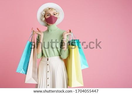 Spring shopping during quarantine conception: fashionable woman wearing protective mask posing with colorful paper bags. Pink background. Copy, empty space for text