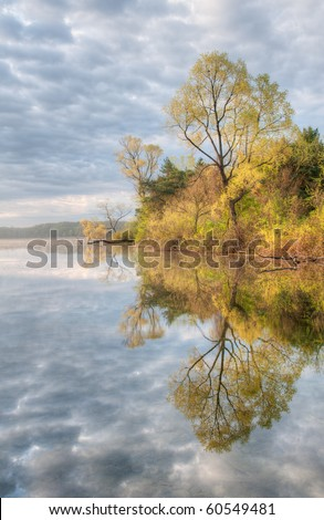 Spring shoreline of Whitford Lake with beautiful clouds and reflections in calm water, Fort Custer State Park, Michigan, USA