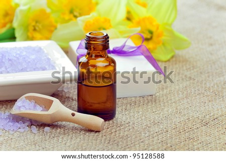Spring spa: bath salt with soap and essential oil, closeup shot, focus on salt, spoon and bottle