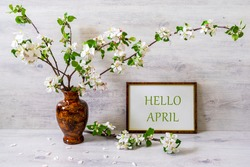 Spring still life with branches of blossoming apple tree in vase with photoframe on light background. White hotoframe with text HELLO APRIL. April is coming, springtime concept