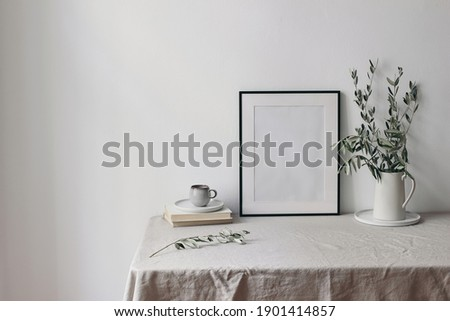 Spring, summer breakfast still life scene. Cup of coffee, books and empty black picture frame mockup. Beige linen tablecloth. Olive tree branches in ceramic jug. Farmhouse, Scandinavian interior.
