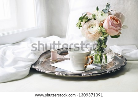 Spring, summer still life scene. Cup of coffee, blank greeting card, envelope on old silver tray at windowsill. Vintage feminine styled photo. Floral composition, pink English roses and Ranunculus.