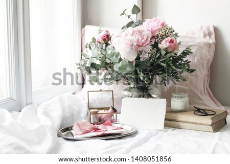 Spring, summer wedding still life scene. Blank paper card mockup, old books and linen pillow at windowsill. Vintage feminine floral composition. Bouquet of pink roses, peony flowers and eucalyptus.