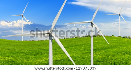 Spring sunny day on a green meadow with wind power generators.